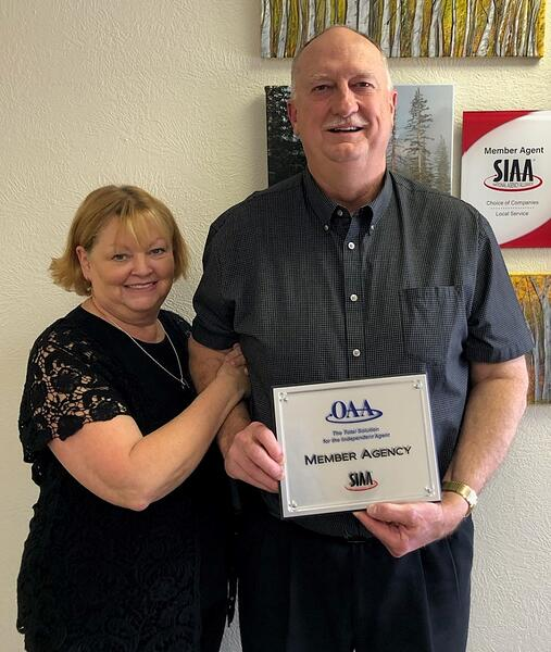 man and woman holding a member agency award