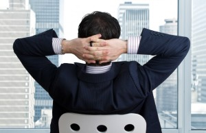 A man relaxing with his hands behind his head taking in the city view after a successful business day.