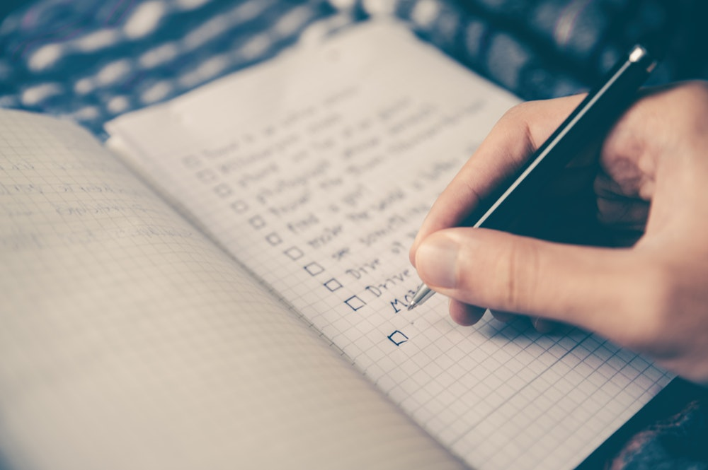 person making a list in a grid notebook