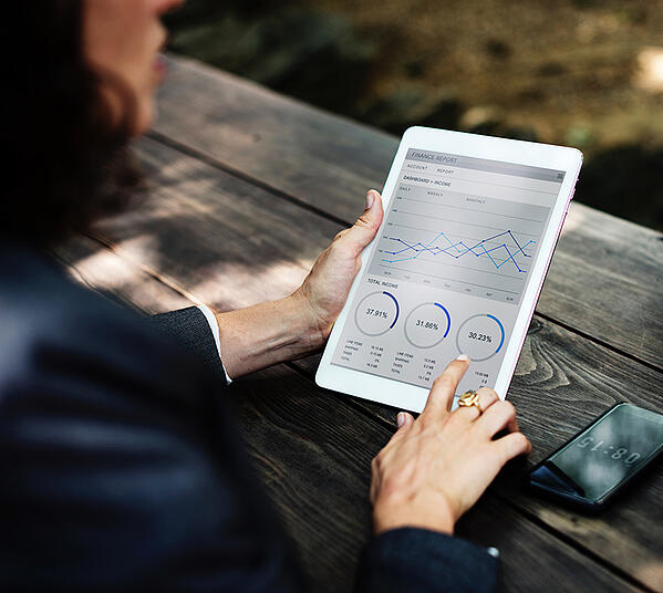 woman holding an ipad with charts and graphs