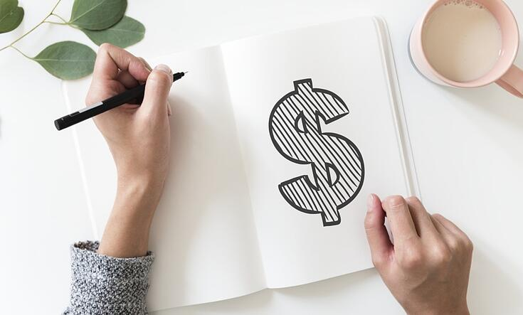 person drawing a dollar sign in a sketch book