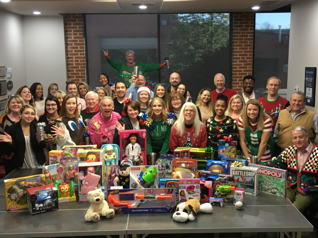 team gathered around a table of toys for Christmas drive