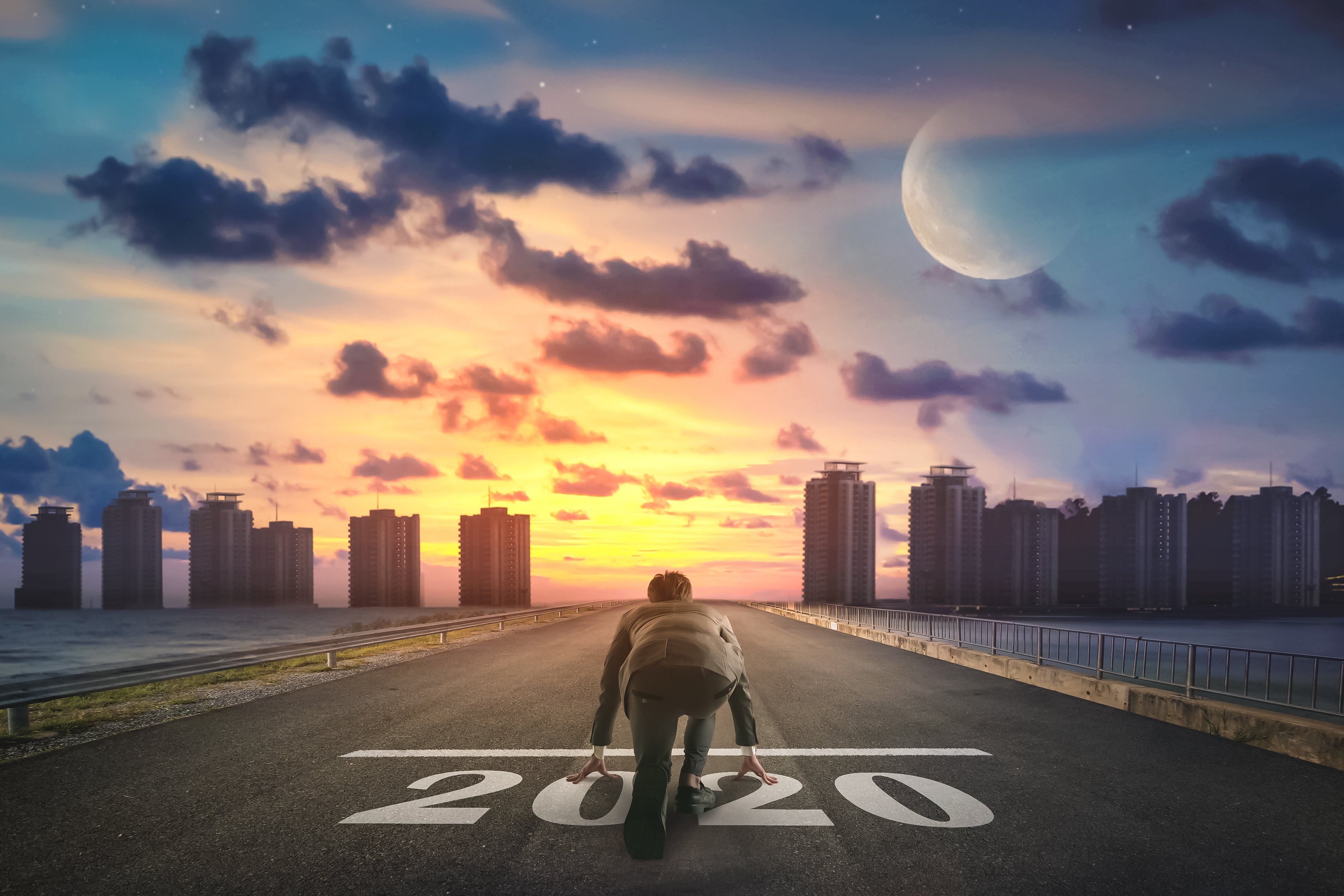 person at a 2020 starting line, looking into a sunset above a city silhouette