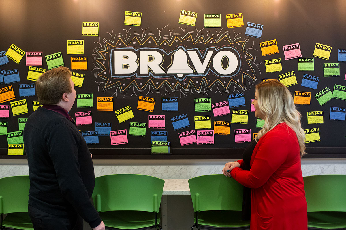 man and woman standing in front of a chalkboard that says BRAVO, surrounding by post it notes