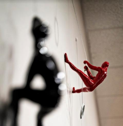 miniature sculpture of a red man climbing a wall