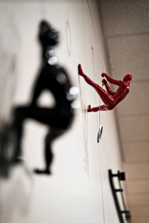 miniature sculpture of a red man climbing a wall