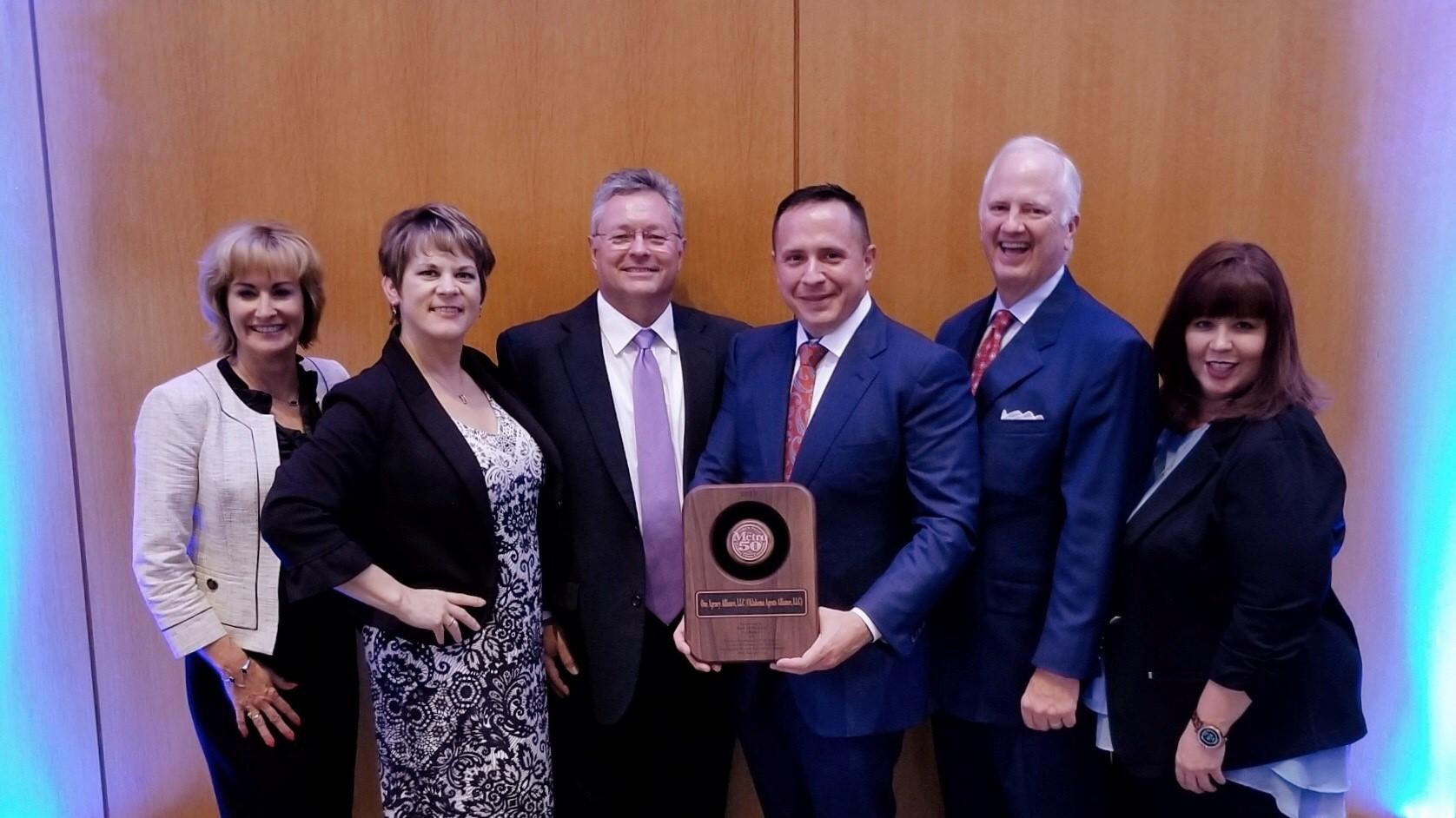 OAA leadership team holding an award