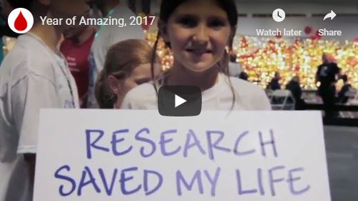 still shot from video: girl holding a poster that says Research saved my life