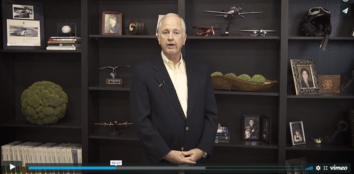 tony caldwell standing in front of bookshelves with various trinkets