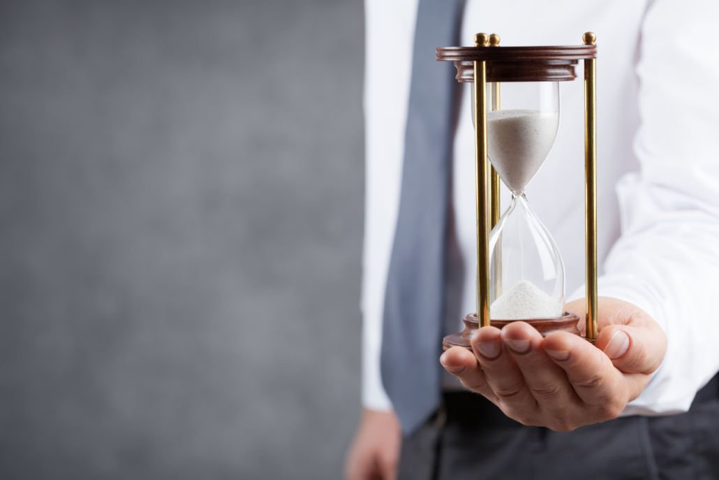 Businessman holding hourglass in his hand. Deadline and time management concept.