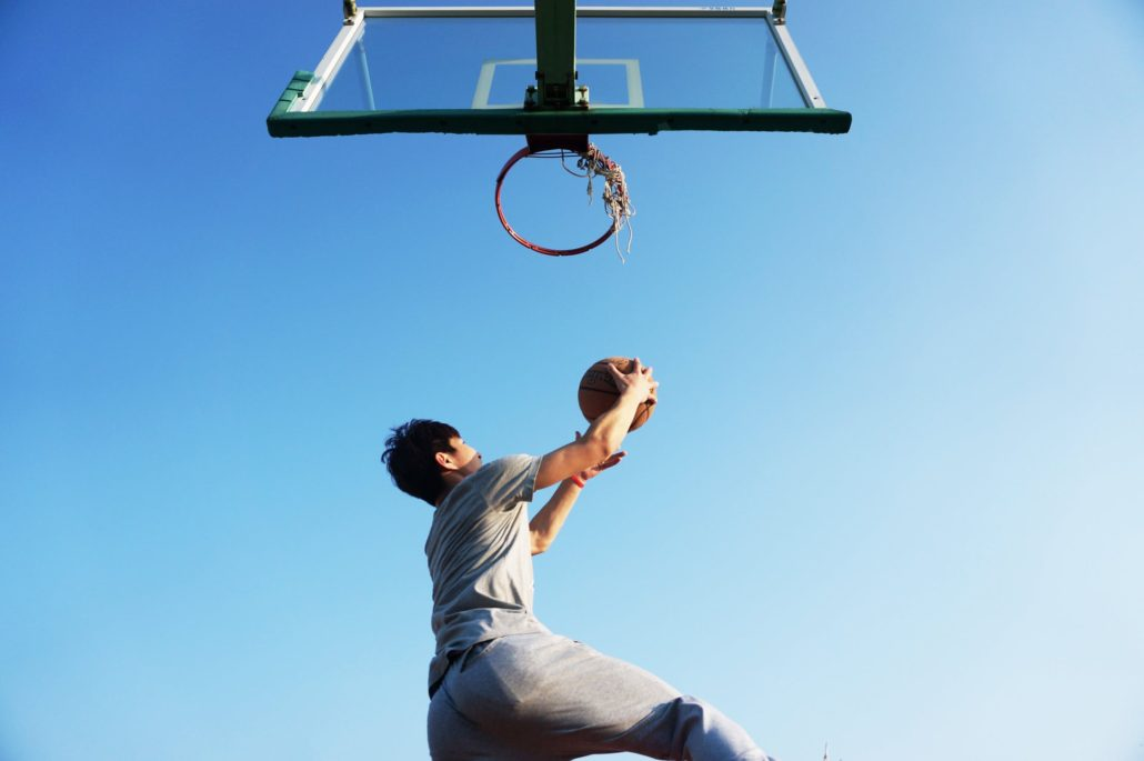 guy under a basketball hoop with a ball, about to throw it in