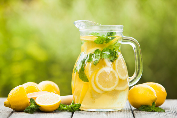 Preparation of the lemonade drink. Lemonade in the jug and lemons with mint on the table outdoor
