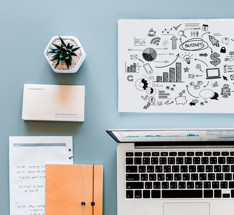 view of a workspace with a laptop, notebooks, growth chart, and plant