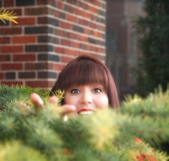 girl peeking over a bush with just most of her face visible