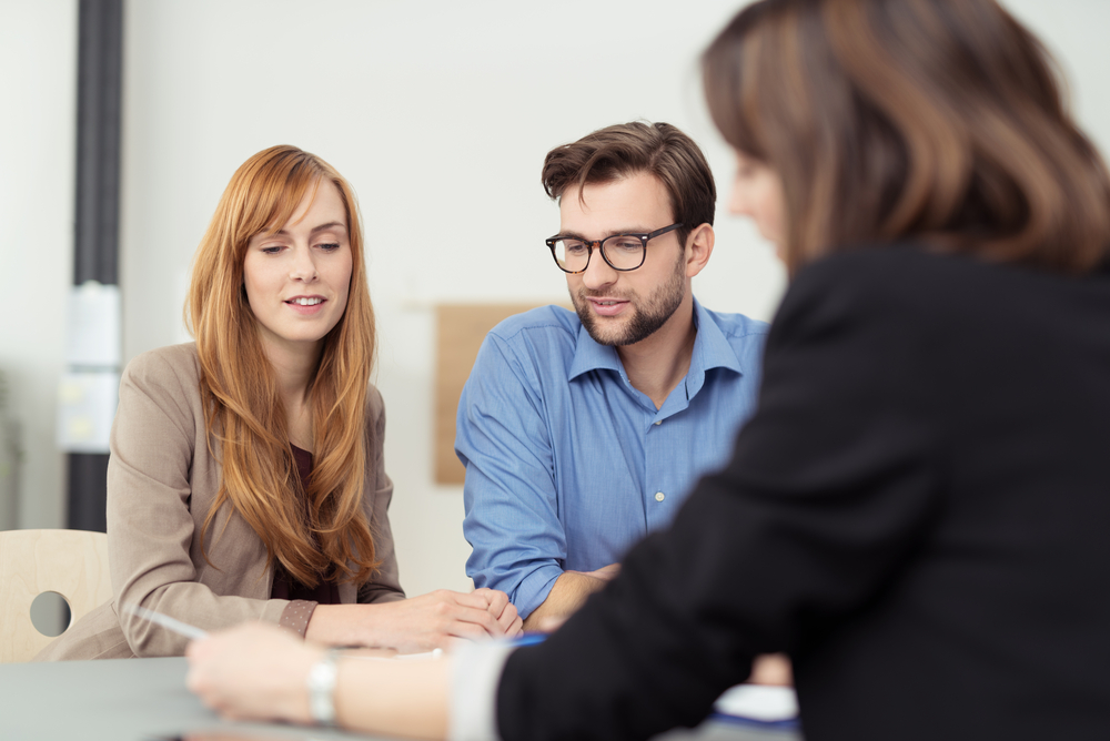 man and woman meet with another woman in a small office