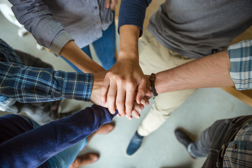 Group of people joining hands as a symbol of partnership