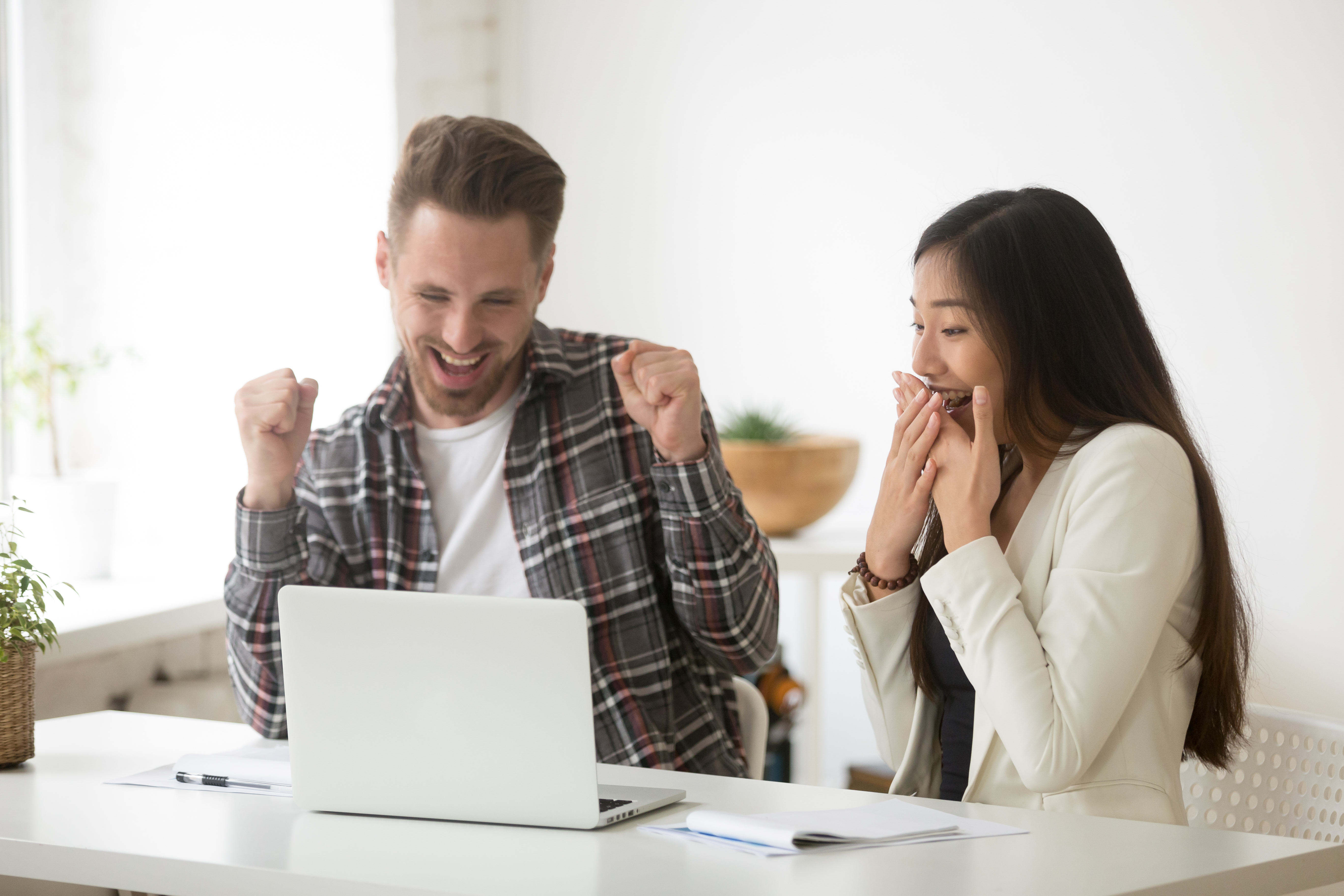 man and woman in front of a laptop looking very excited